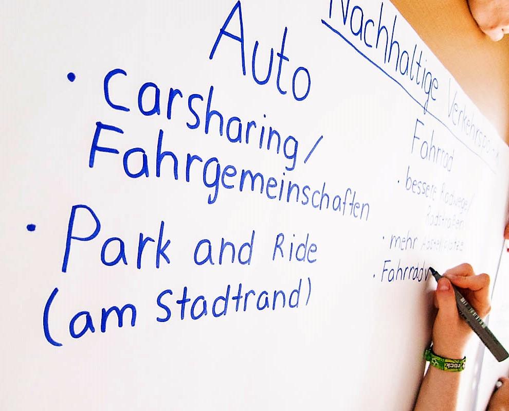 Schüler schreibt gerade Aufzählungspunkte auf ein Plakat