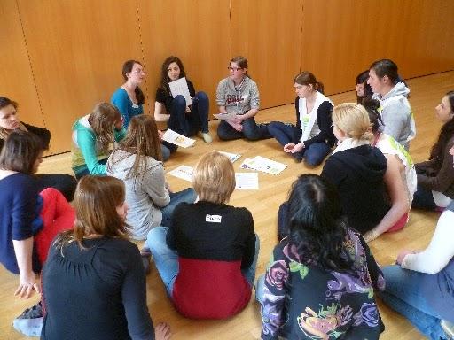 TeilnehmerInnen sitzen in einem Sitzkreis am Boden