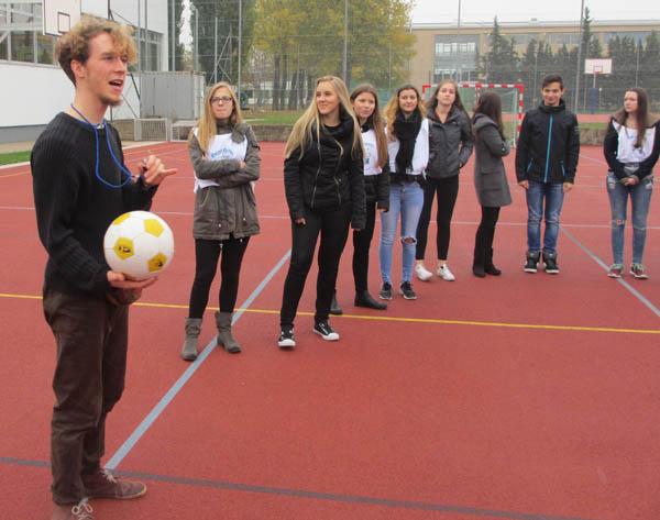 Workshopleiter steht mit den Schülern auf dem Fußballplatz